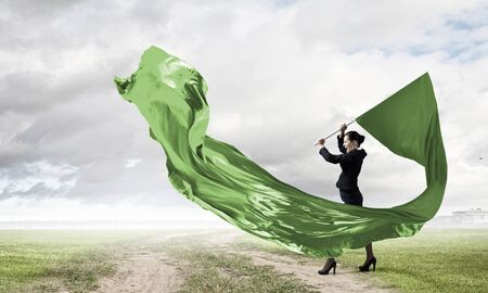 Determined businesswoman waving flag as symbol of power