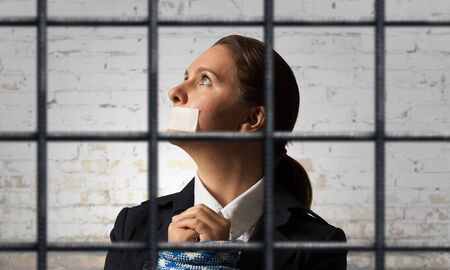Young businesswoman with tape on mouth and tired hands