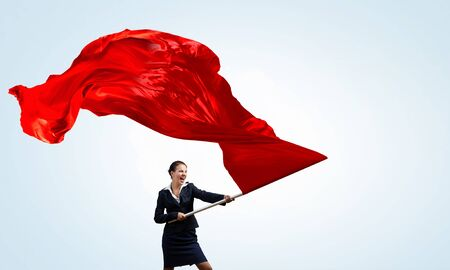 Determined businesswoman waving flag as symbol of women power Stock Photo