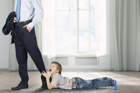 stay home work: Young boy hugging his fathers leg and crying