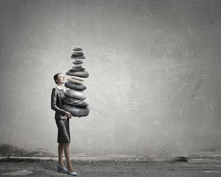 oppressed: Attractive businesswoman carrying stack of stones in hands