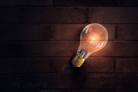 turned: One turned on light bulb on brick wall background
