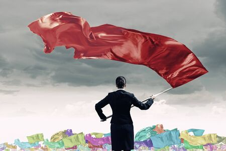 Determined businesswoman waving flag as symbol of women power