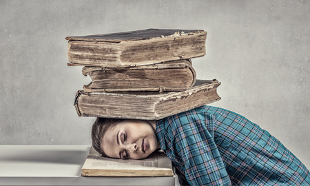 oppressed: Student girl pressed with pile of books to table