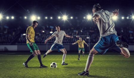 Football players at stadium field fighting for ball Stock Photo