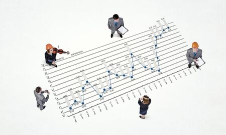 dynamic growth: Top view of business people and graphs and diagrams on floor