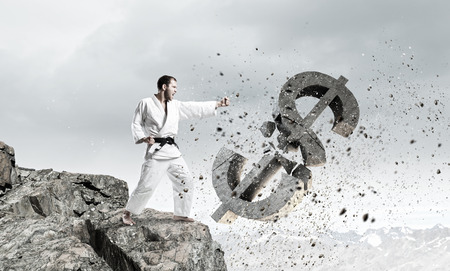 decreasing: Young determined karate man breaking with leg concrete dollar sign