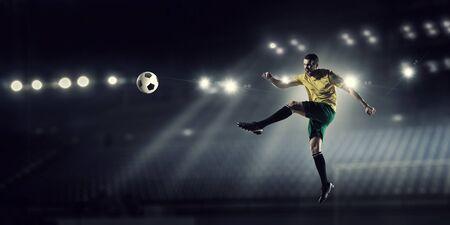 Determined football player at stadium hitting ball Stock Photo