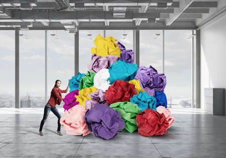 hard to find: Young woman and heap of paper balls as symbol of creativity