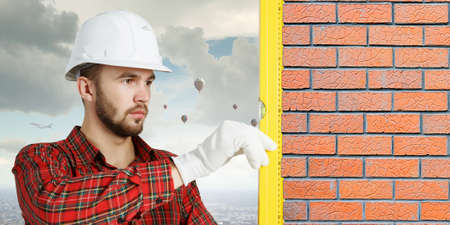 Builder man in checked shirt using measuring level