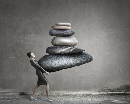 Attractive businesswoman carrying stack of stones in hands