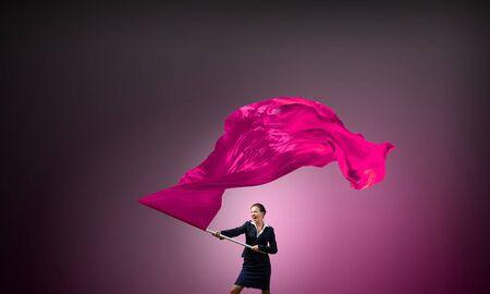 revolutions: Determined businesswoman waving flag as symbol of women power Stock Photo