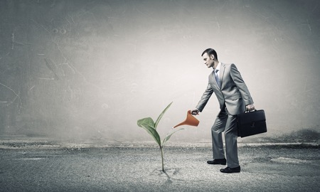Young businessman watering green plant with can Stock Photo