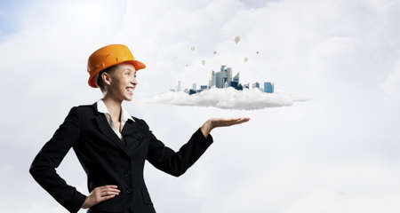 woman engineer: Woman engineer in hard hat showing construction project Stock Photo