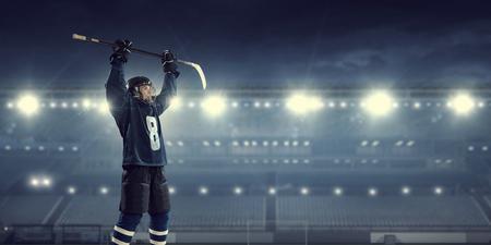 Hockeyspeler in blauw uniform op ijsbaan in schijnwerpers
