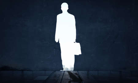 key to freedom: Dark wall and silhouette of businessman as doorway Stock Photo