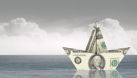 Ship of dollar banknote floating on water