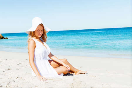 Portrait of young pretty woman relaxing on sandy beach
