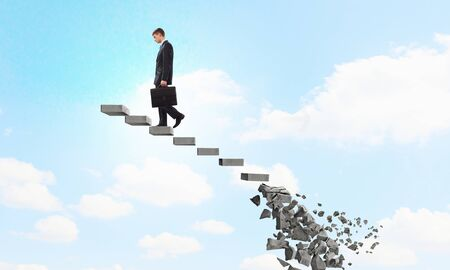 collapsing: Businessman climbs steps of collapsing financial ladder Stock Photo