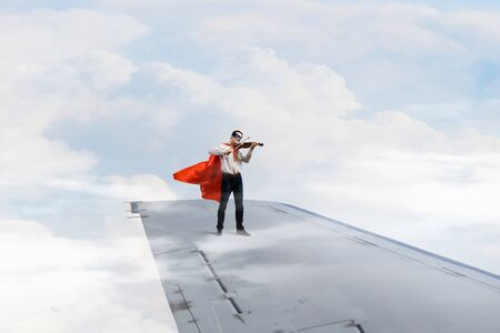 super man: Super man standing on edge of airplane wing playing violin Stock Photo