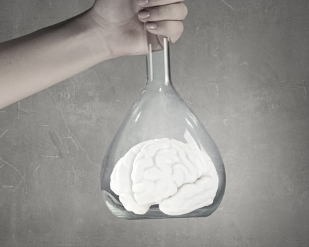 laboratorian: Hand holds flask with image of human brain