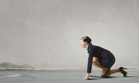 compete: Young determined businesswoman standing in start position ready to compete