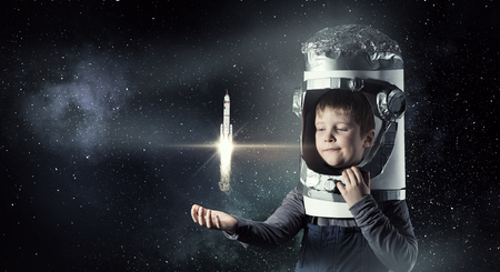 Cute kid boy with carton helmet on head dreaming to become astronaut Banco de Imagens