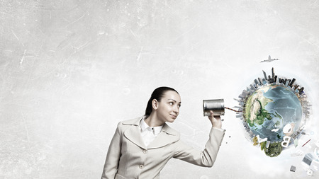 Young businesswoman using tin can and string as communication tool. Elements of this image are furnished by NASA 版權商用圖片
