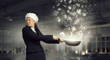 melodist: Pretty businesswoman in suit and cook hat with pan in hand