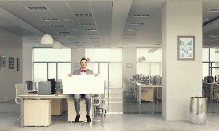place of research: Young businessman sitting on table holding white blank banner in modern office