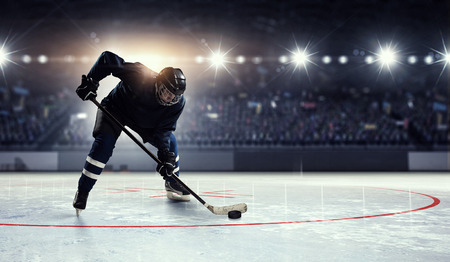 competitive: Hockey player in blue uniform on ice rink in spotlight