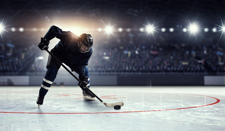 Hockey-Spieler in der blauen Uniform auf der Eisbahn im Scheinwerfer