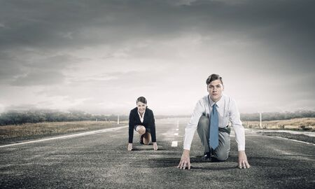 Young determined businesspeople standing in start position ready to compete