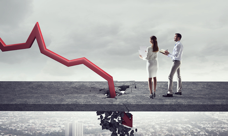 the collapsing: Businesspeople and red decreasing arrow breaking through floor