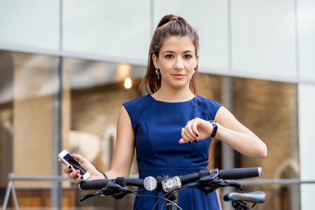 hectic: Pretty business woman looking at watch being outside Stock Photo