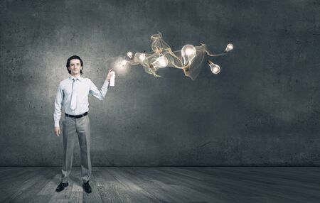 aerosol can: Young businessman spraying glass bulbs from aerosol can as symbol of creative ideas Stock Photo