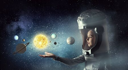 become: Cute kid girl with carton helmet on head dreaming to become astronaut Stock Photo