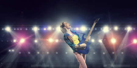 bass guitar women: Young attractive rock girl with electric guitar on stage