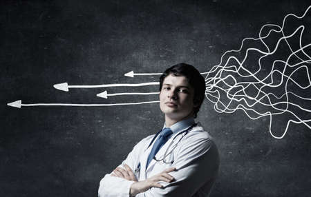 medical decisions: Young man doctor on concrete background and thoughts coming out of his head Stock Photo