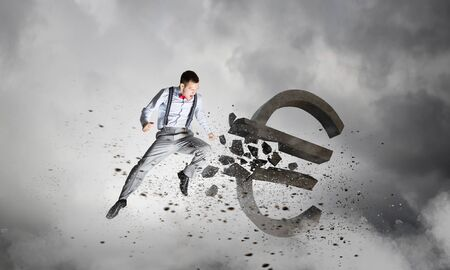 Determined businessman in anger breaking stone euro sign Stock Photo