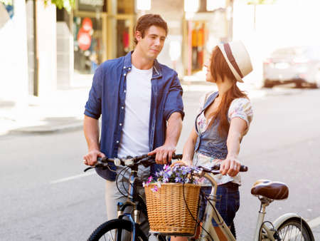 Happy young couple in city with bike