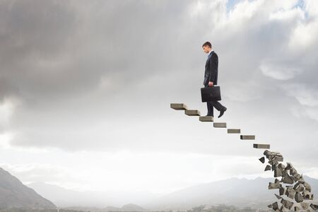 Businessman climbs steps of collapsing financial ladder Stock Photo