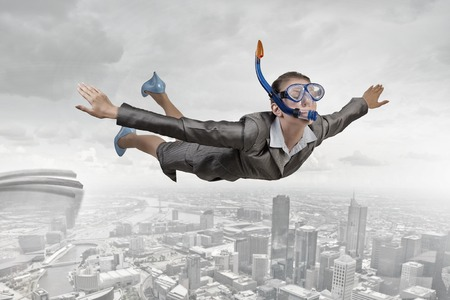 risky job: Young businesswoman in suit and diving mask flying in sky