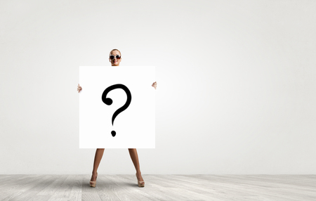 Young woman in sunglasses showing white banner with question mark
