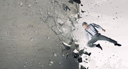 fedup: Emotional businessman breaking stone wall with karate punch Stock Photo