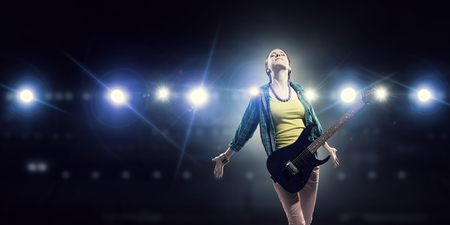 Young attractive rock girl with electric guitar on stage