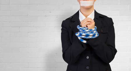 accused: Young businesswoman with tape on mouth and tired hands