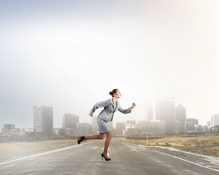 Young businesswoman in suit running on asphalt road