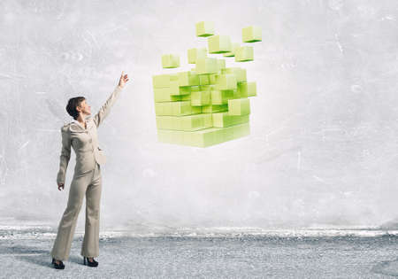 Businesswoman reaching hand to touch 3D rendering cube figure