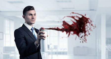 aerosol: Young businessman in modern interior spraying color paint from aerosol Stock Photo